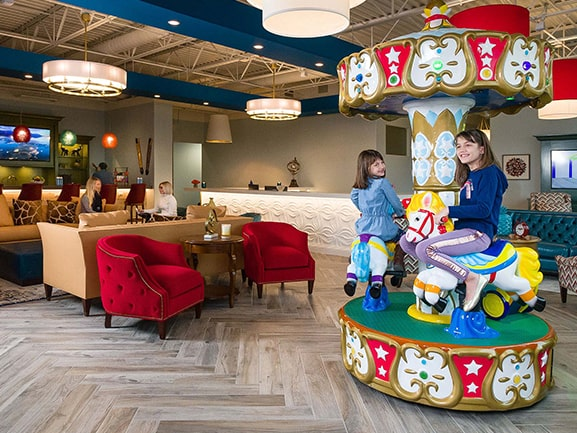 2 children enjoying a ride in the lobby